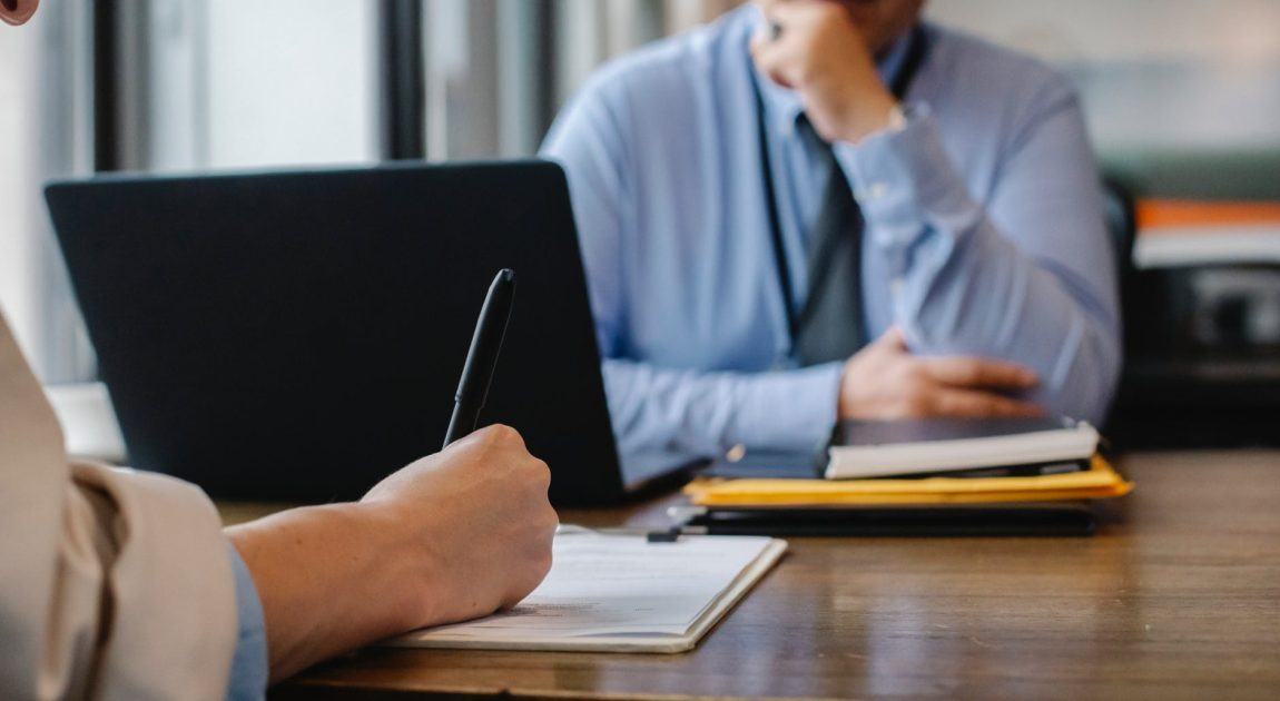 woman filling job application form in office with boss